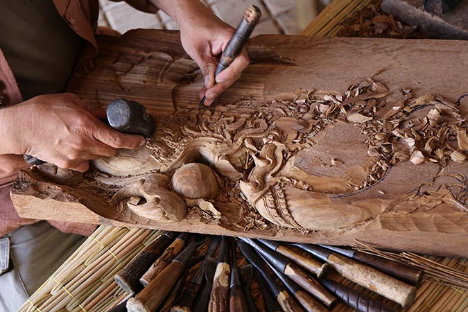 a-carpenter-hands-working-with-a-chisel-and-carving-tools-on-wooden-workbench