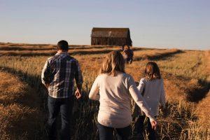 Family walking in grassy field