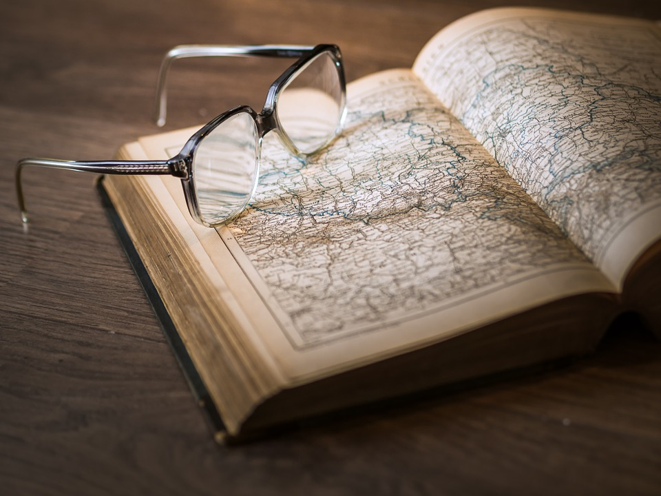 Reading glasses resting on map book