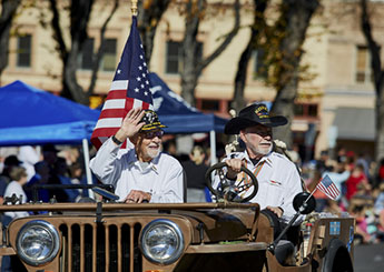 Two men in Veterans Day Parade with American Flag