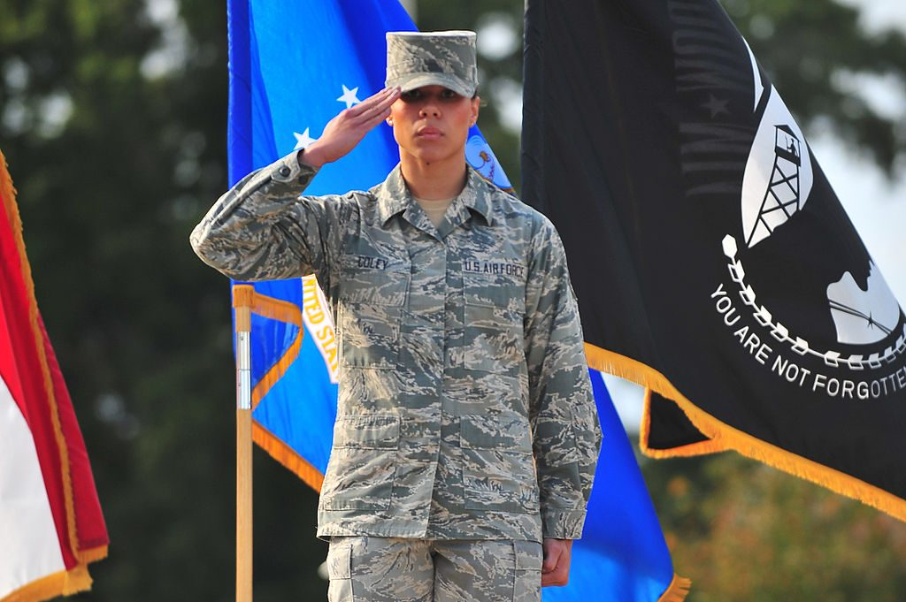 Soldier saluting in front of flags