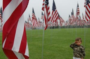 Young boy surrounded by american flags