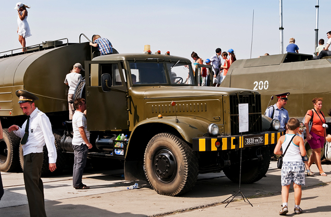 Families looking at military vehicles