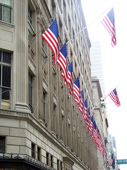 Row of american flags on flagpoles city building