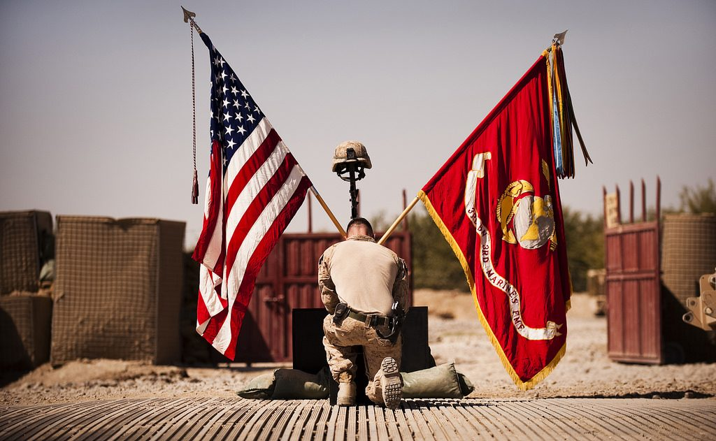 marine kneeling before marine corps and american flags
