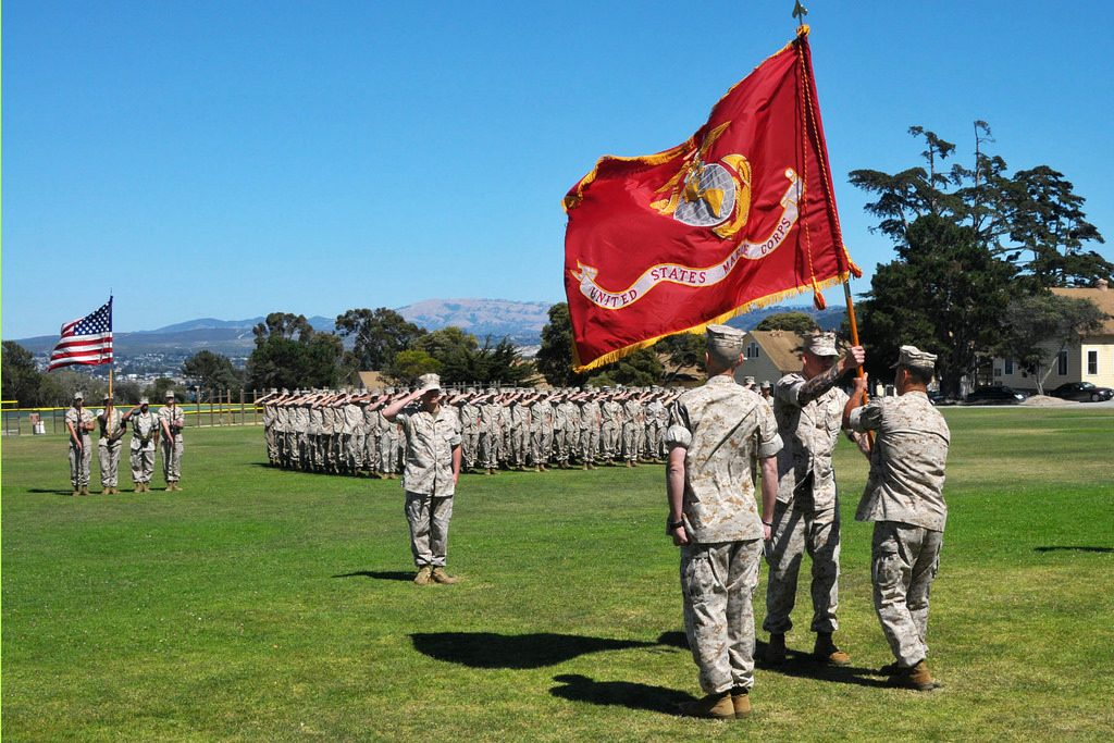 marines carrying marine corps flag outdoors