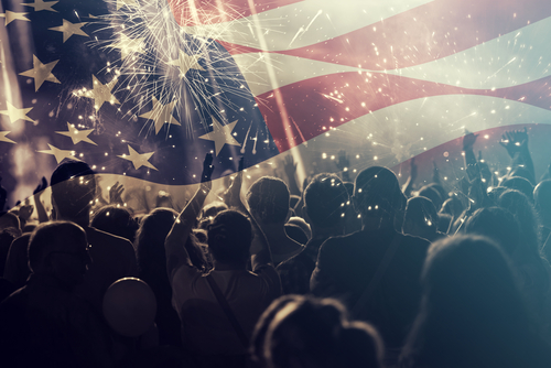 Crowd of people celebrating Independence Day. United States of America USA flag with fireworks background for 4th of July
