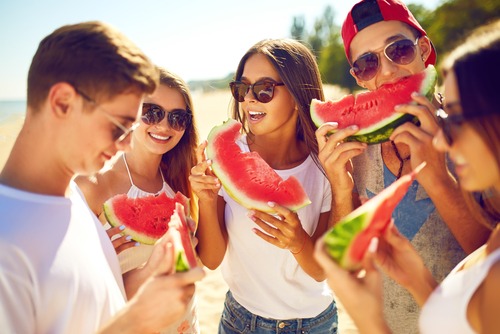 Group of friends having fun eating watermelon. on the beach 4th of july