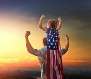 Patriotic holiday. Happy family, father and his daughter child girl with American flag outdoors on background sunset cityscape. USA