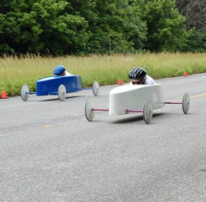 Two soap box derby drivers speed down the race track.