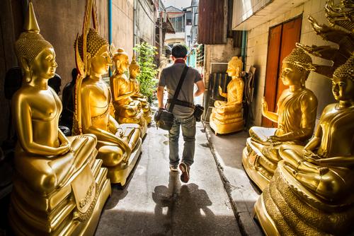 Man was walking through golden buddha road.Bangkok Thailand