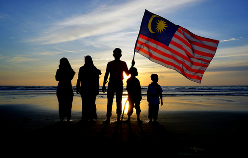 Silhouette of family with waving a Malaysian flag at beach. independence day merdeka day.