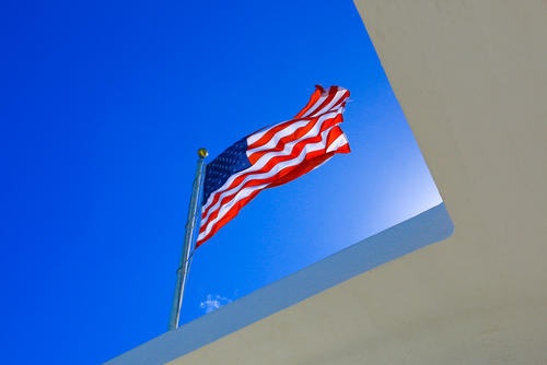The US flag flies above the USS Arizona Memorial in Pearl Harbor