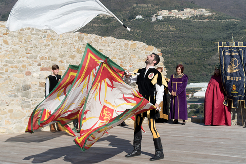 Flag throwing during medieval festival in the historic city of Taggia
