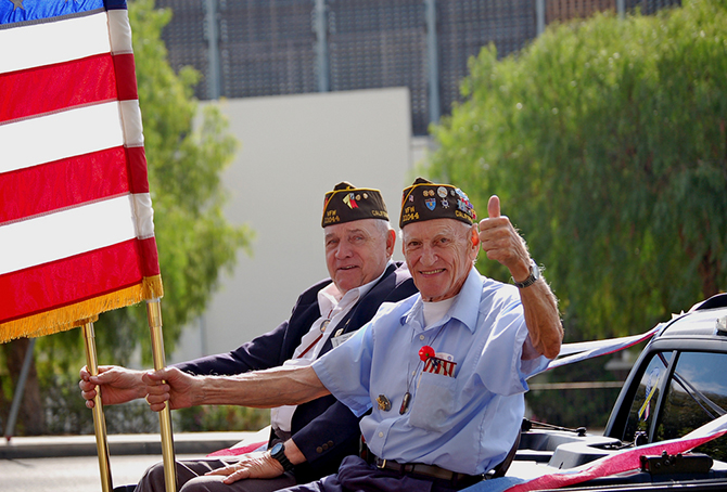 veterans holding american flag in parade