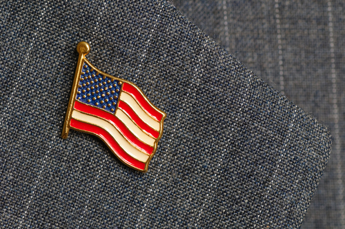 An American flag lapel pin on a pinstripe suit