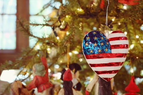 Heart shaped United States flag ornament hanging on Christmas tree
