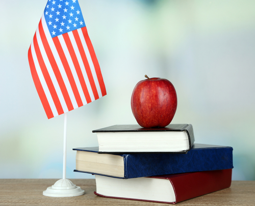 American flag books and apple on wooden table