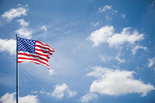 american flag flying blue sky