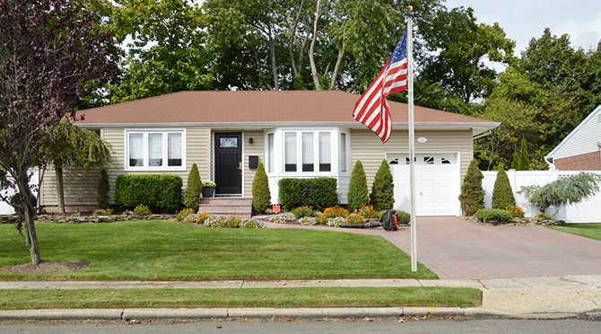 american flag waving front ranch house