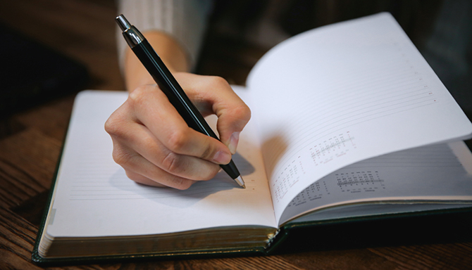 person writing notebook