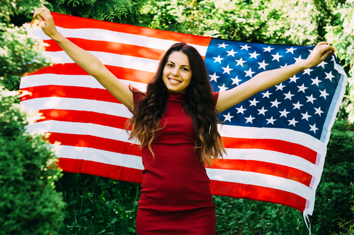 Beautiful girl with a US flag in the par
