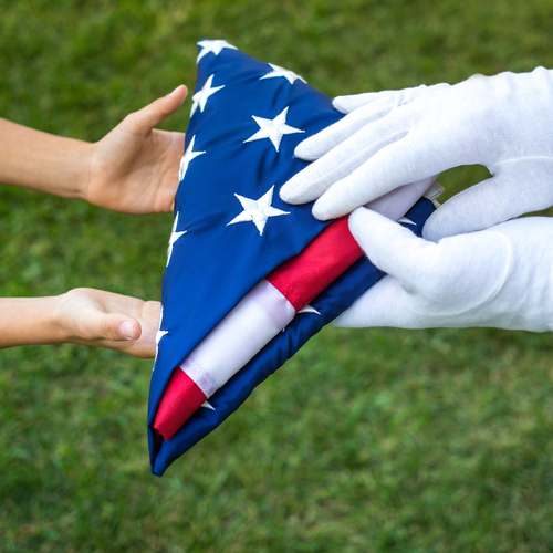 Closeup hands hold american flag carefully folded over green background