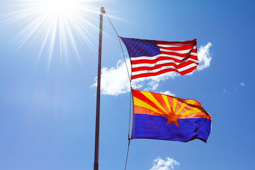 Flags of the United States and the Navajo Reservation are flying against the shining sun and clouds