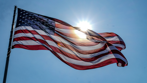 wonderful shot of waving american flag with the sun behind
