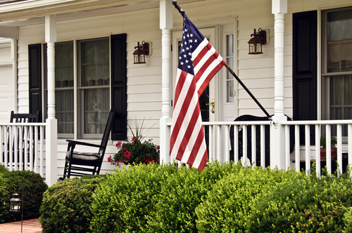 front porch white colonial home american flag