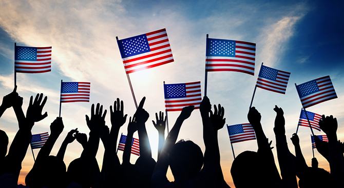 group people waving american flags sunset