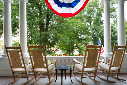 wooden rocking chairs lined up on a patio overlooking a lush garden below a draped American flag