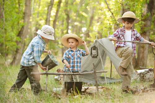 three boys build tent campfire